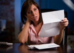 Young woman is frustrated going through correspondence.