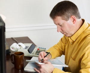Mature man taking data off the computer for doing income taxes