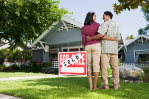 Couple with sold sign and house