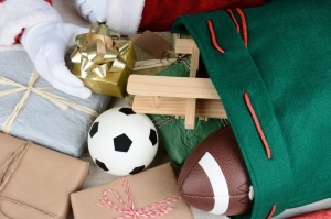 Closeup of Santa Claus filling his bag with toys and presents. Only Santa's hands are visible. Wrapped presents soccer ball, football, toy airplane and gifts fill the frame. Horizontal format.