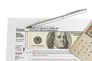 Tax form with paper money, silver pen, calculator on white background